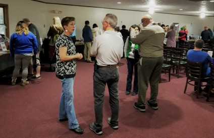Neighbors meet and mingle as the Silent Auction gets going.
